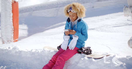 snowbank: Woman in snowsuit with snowboard sitting on snowbank texting during bright sunny day
