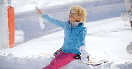 afro hairdo: Happy young woman with a fun afro hairdo posing for a winter selfie sitting in thick winter snow at a ski resort