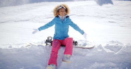 pants down: Beautiful young woman with blond curly hair  pink pants and ski clothes sitting on snowboard stuck in the snow after falling down