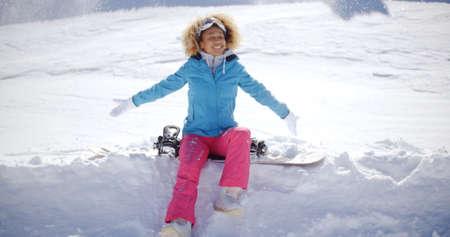 pantalones abajo: Hermosa mujer joven con los pantalones pelo rizado rubio rosa y ropa de esquí que se sientan en snowboard clavados en la nieve después de caerse