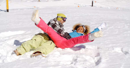 frolic: Young couple in ski clothes enjoying a frolic in the snow lying on their backs laughing and kicking their feet in the air