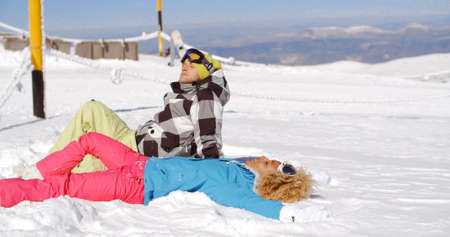 slopes: Young man and woman in skiing outfits laying back to rest in snow on mountain after a busy day on the slope Stock Photo
