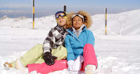 slopes: Attractive young man and woman in skiing outfits sitting in the snow on mountain after a busy day on the slope