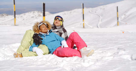 blissfully: Affectionate young couple enjoying the fresh winter snow at a ski resort lying in the fresh white powder smiling blissfully as they relax in the sun