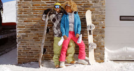 Cute couple in snowsuits standing closely together next to upright snowboards while they lean against ski resort garage in thick snow on sunny day Stock Photo
