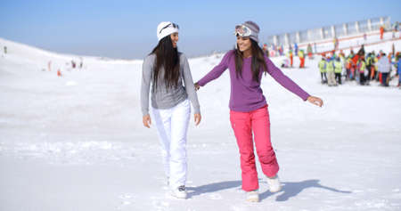 ski walking: Two attractive young woman walking in fresh snow at a winter ski resort chatting and smiling together in the sunshine  with copy space