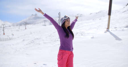 jovenes felices: Happy young woman celebrating her winter vacation standing on a snowy mountainside with her arms outstretched smiling with happiness and bliss Foto de archivo