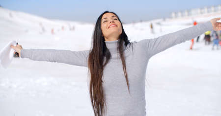 head tilted: Young woman rejoicing in the winter weather standing in fresh snow at a ski resort with her arms open and head tilted back smiling at the sun. Stock Photo