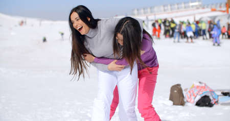 frolicking: Two playful attractive young woman frolicking in the snow at a winter resort laughing and joking as they goof around Stock Photo