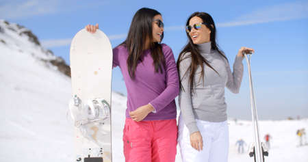 winter vacation: Cute sisters in long black hair standing with snowboards and looking at each other through sunglasses near ski slope in winter