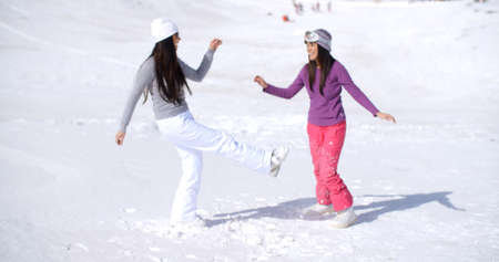 frolicking: Two young woman frolicking in fresh deep white winter snow at a mountain resort enjoying the fresh air and sunshine