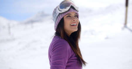 slopes: Happy beautiful young woman on a snowy mountain slope wearing a knitted cap and her goggles on her forehead smiling happily as she looks up into the air  close up view.