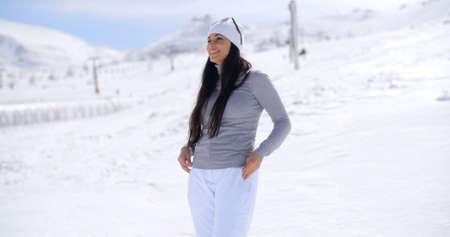 adentro y afuera: Atractiva mujer joven de pie en la nieve invierno en una estación de esquí de montaña de pie en una pendiente con vistas sobre el paisaje con sus gafas de sol en la mano, con copia espacio.