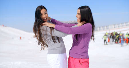 strangling: Pair of female friends or sisters laughing while pretending to be strangling each other on ski slope with group of people watching in the background