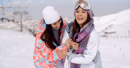 inter: Two happy playful young ladies at a ski resort standing grinning at the camera in a snow inter landscape with copy space