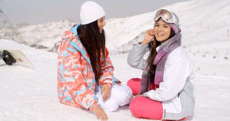 valley below: Two attractive young female friends sitting chatting in the snow with their snowboards overlooking a snowy valley and ski lift below