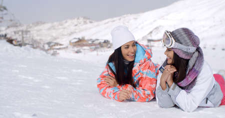 giggling: Cute pair of female twins in long black hair and ski clothing giggling while laying down on ground at bottom of ski slope with mountain behind them. Stock Photo