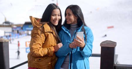 mujeres morenas: Dos sonrientes mujeres adultas jóvenes lindos en marrón largo pelo negro y chaquetas azules que miran un teléfono celular mientras está de pie delante de una pista de esquí.