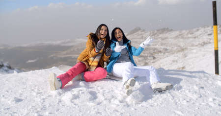 frolicking: Two young women frolicking in the snow as they sit on a mountain summit at the edge of a ski run laughing merrily
