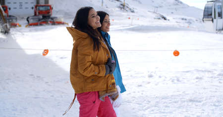 ski walking: Two young women walking through snow at a winter ski resort smiling and chatting as they enjoy their vacation  with copy space Stock Photo