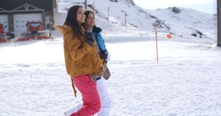 enjoy space: Two young women walking through snow at a winter ski resort smiling and chatting as they enjoy their vacation  with copy space Stock Photo