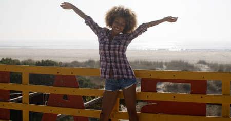 mujer alegre: chica joven que se separa las manos y alegría con la orilla del mar en el fondo
