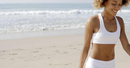slow motion: African american woman in sportswear going away from sea in slow motion