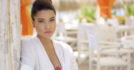 white robe: Attractive single young woman in white robe with sultry or disappointed expression standing near wooden patio with dining tables and chairs outdoors