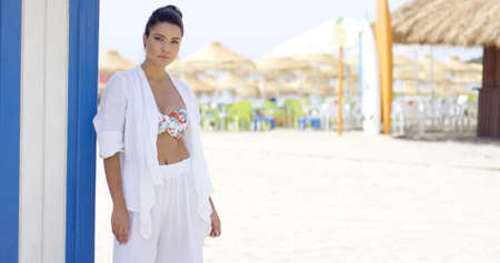 house robe: Beautiful single woman in white robe with cheerful expression standing outdoors near beach house and beachgoers