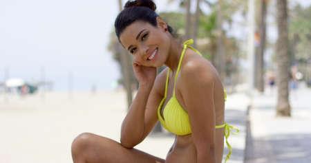 sea beach: Cute woman with tied back black hair and yellow bikini resting head on hand while sitting on wall near beach