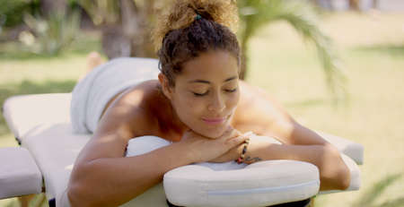 massage table: Grinning woman wrapped in white towel with folded hands under chin laying down on massage table outside Stock Photo