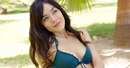 asian sexy girl: Attractive young woman with a lovely friendly smile sitting in the shade of a tropical palm in her bikini enjoying her summer vacation