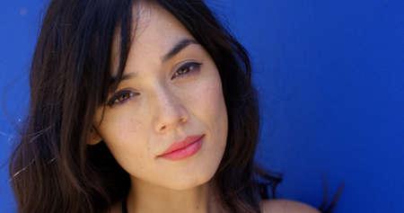ojos marrones: Cerca de la mujer con los ojos marrones y el pelo largo mirando serenamente a la cámara junto a un fondo azul