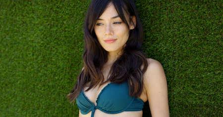 bikini top: Beautiful young woman wearing green bikini top and having long brown hair lays in lush green grass Stock Photo