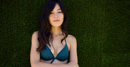 bikini top: Beautiful woman wearing green bikini top lays in grass and smiles contently at the camera