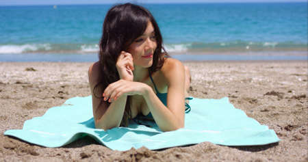 liesure: Pretty woman lying on a towel facing the camera sunbathing on a tropical beach with a lovely friendly smile on her face
