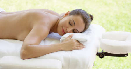 lays down: Disrobed woman lays belly down on table as she relaxes while waiting for masseuse