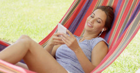 liesure: Pretty young woman relaxing in a colorful striped hammock in the garden listening to music on her mobile phone or storage device Stock Photo