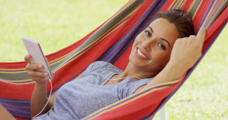 liesure: Happy young woman listening to music in a hammock outdoors in a sunny summer garden with a smile of pleasure Stock Photo