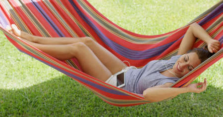 liesure: Happy young woman relaxing in a colorful hammock outdoors in the shade in the garden looking up at the camera with a smile as she listens to music on her mobile.