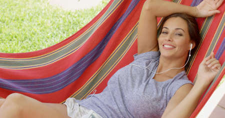 liesure: Blissful young woman relaxing listening to music in a colorful striped hammock outdoors in the garden looking at the camera with a happy smile Stock Photo