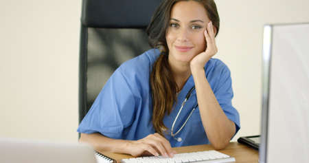 deep thought: Serious female doctor with stethoscope and serious expression while folding arms in deep thought Stock Photo
