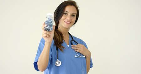 phisician: Young brown haired doctor in scrubs holds bottle towards camera against a light colored background Stock Photo
