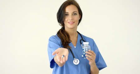 phisician: Attractive young female doctor or nurse holding out a capsule in the palm of her hand towards the camera  with copy space Stock Photo