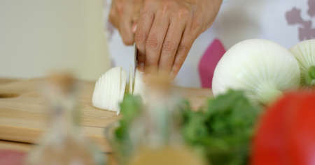starchy food: Close up on female hands cutting fresh onion or other starchy white food on table