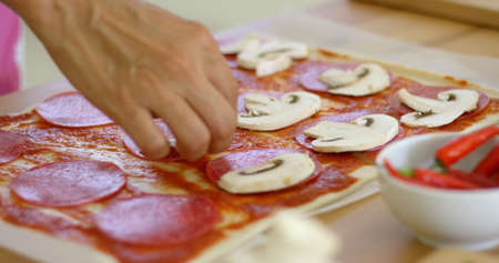 by placing: Woman making a delicious homemade pepperoni pizza placing sliced mushrooms on the salami and tomato paste on her freshly rolled dough crust