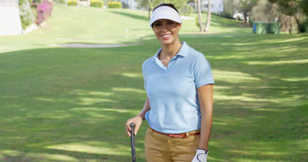 Young woman golfer strolling across the golf course with her club over her shoulder a a happy smile as she looks off to the side