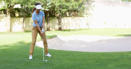lining up: Woman golfer about to play a stroke on the green lining up her ball with the flag in the hole in an active lifestyle concept