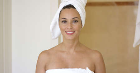 bathroom women: Smiling brunette wearing white towel on head as she steps out of bathroom Stock Photo