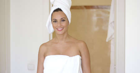 exits: Woman wrapped in towel smiles at camera as she exits the bathroom in a bright afternoon